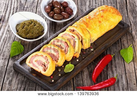 cheese spicy meat Roll-Ups on dark board with basil leaves pepper. Sauce pesto and kalamata olives in gravy boats on background close-up view from above