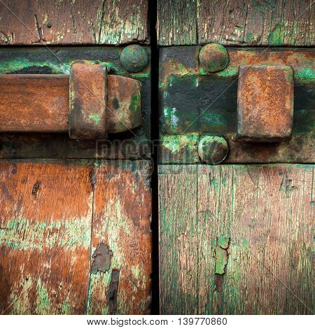 Old gate locked with a rusty iron latch