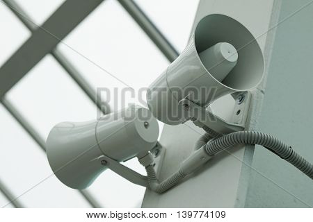 Two twin megaphone on the wall of a building.
