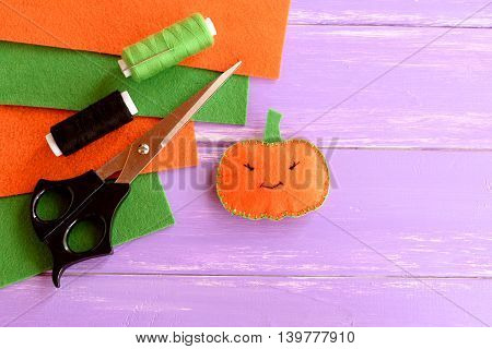 Cute felt pumpkin decor, threads, scissors, needle, felt sheets on lilac wooden background with copy space for text. Halloween sewing crafts for kids. Easy project for Halloween pumpkin