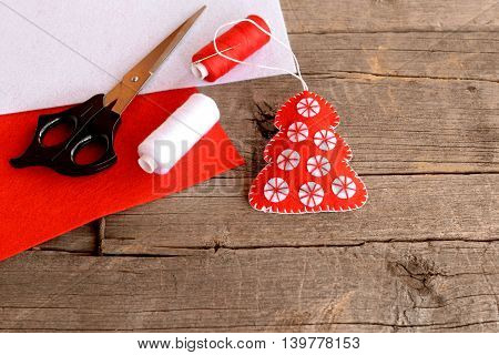 Red felt Christmas tree decor, scissors, red and white felt sheets, thread, needle on wooden background with empty space for text. Home sewing crafts. Beautiful and quick decoration idea for Christmas
