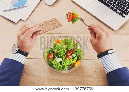 Business lunch at working place. Businessman in office. Healthy, diet food, vegetable salad with apple and juice. Cell phone, laptop and papers, fitness bracelet on hand. Top view, flat lay