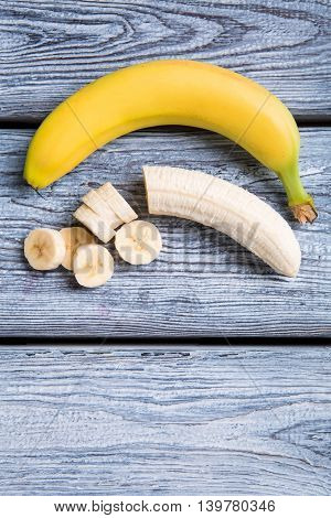 Sliced banana on wooden background. Top view of bananas. Ingredient of organic dessert. High amount of vitamins.