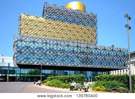 BIRMINGHAM, UNITED KINGDOM - JUNE 6, 2016 - Front view of the Library of Birmingham in Centenary Square with people sitting on benches in the foreground Birmingham England UK Western Europe, June 6, 2016.