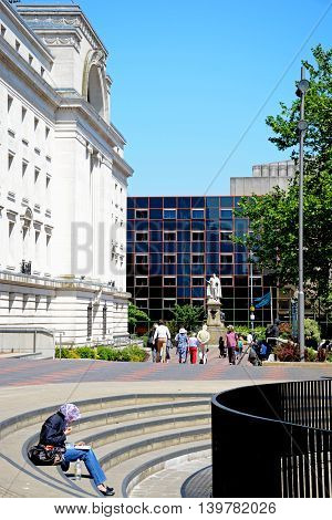 BIRMINGHAM, UNITED KINGDOM - JUNE 6, 2016 - View of Baskerville House to the left hand side in Centenary Square with a woman sitting on the steps having lunch in the foreground Birmingham England UK Western Europe, June 6, 2016.