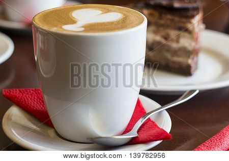 A latte mug with a spoon, a red serviette on a saucer.
