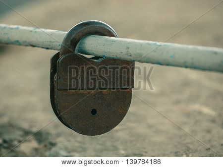 Shut up old worn rusty shabby padlock hanging on painted worn cut pipe outdoors