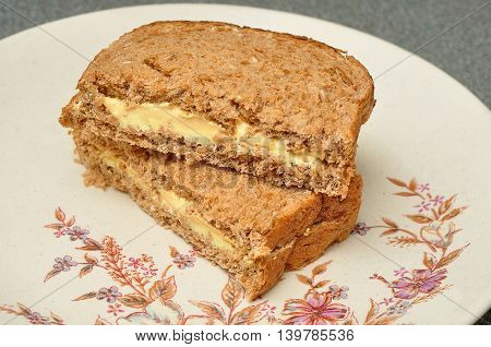 A cheese spread whole wheat sandwich on a plate
