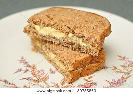 A cheese spread whole wheat sandwich with shallow dept of field