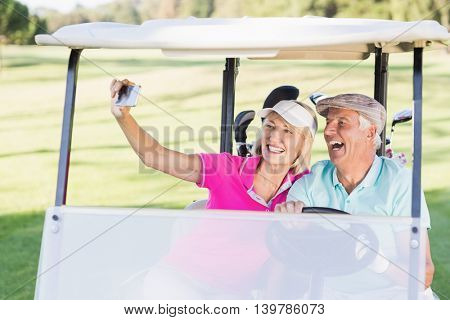 Happy mature couple taking selfie while sitting in golf buggy