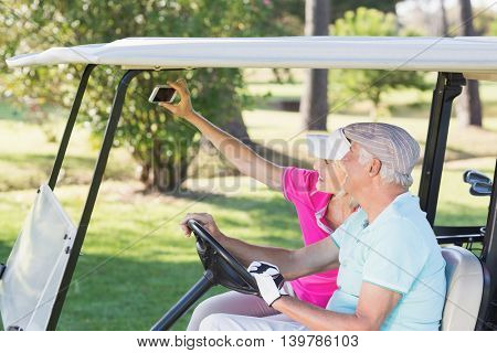 Smiling mature couple taking self portrait while sitting in golf buggy
