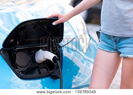 So efficient and comfortable. Close up of a hand of a woman touching a fuel tank while charging her electric car on the street