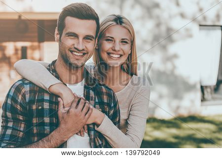 Lovely couple. Beautiful young couple bonding to each other and smiling while standing against their new house