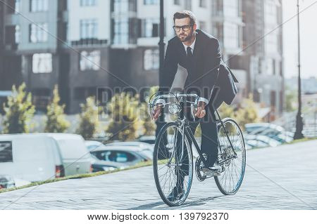 On the way to his office. Full length of handsome young businessman looking forward while riding on his bicycle