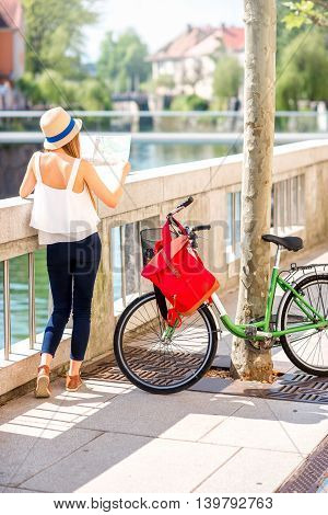 Young female tourist standing with paper map near the bicycle in Ljubljana city, traveling in Slovenia. Back view with copy space