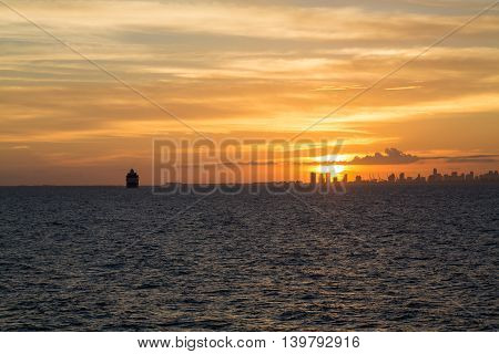 Miami skyline at sunset from the sea with freighter on the horizon