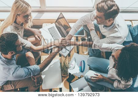 Strong business team concept. Top view of four happy young people holding hands clasped while sitting at the wooden desk together