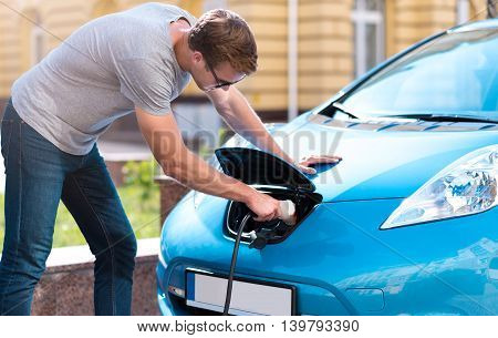 I have no problem with it. Handsome young man plugging his eco car for charging a battery in the city