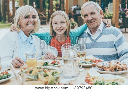 Enjoying nice time with grandparents. Happy little girl embracing her grandparents and looking at camera while sitting at the dining table outdoors together