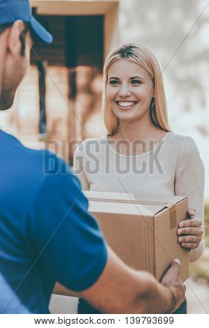 From hands to hands delivery. Beautiful young woman smiling while young delivery man giving a cardboard box to her