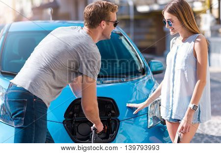 You are welcome. Smiling pleasant man helping beautiful young woman to charge an electric car