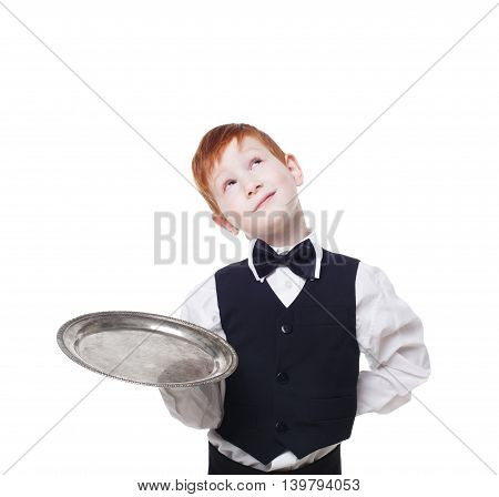 Little waiter thoughtful, dreaming with empty tray. Smiling inattentive redhead child boy in suit play restaurant servant at blue background