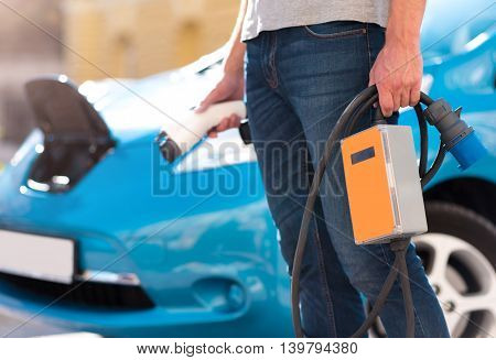 Comfortable for a city. Close up of a man holding a power connector for an electric vehicle in his hand with an electric car on the background