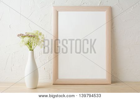 Frame mockup with tender flowers in white stylish vase. Poster white frame mockup. Empty white frame mockup for presentation design.