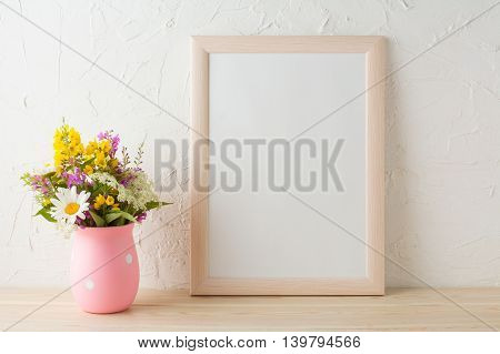 Frame mockup with wild flowers in pink vase. Portrait or poster white frame mockup. Empty white frame mockup for presentation artwork.