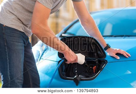 My contribution to save the environment. Close up of hands of a man plugging power cable in his hybrid car to charge the battery