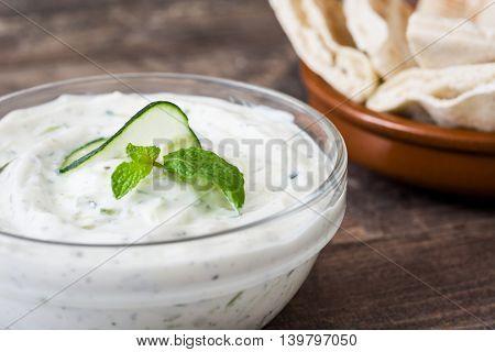 Tzatziki sauce in bowl and fresh ingredients