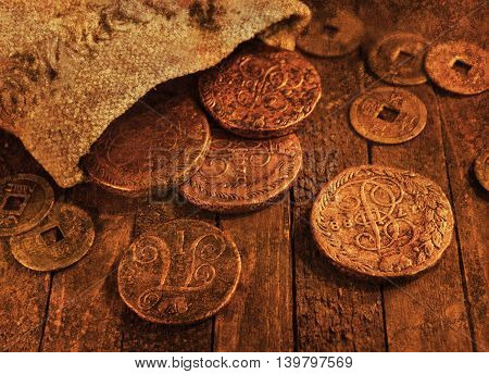 Ancient coins on wooden background with texture effect
