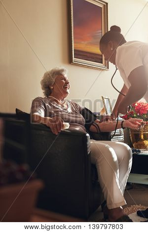 Home caregiver measuring blood pressure of senior patient at home. Female healthcare worker doing routine checkup of a elderly patient.