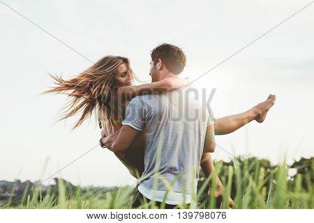 Man Carrying Girlfriend In  Grass Field