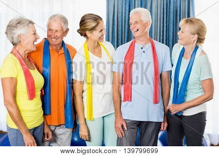Instructor and seniors with stretching bands during sports class