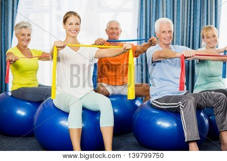 Seniors using exercise ball and stretching bands during sports class