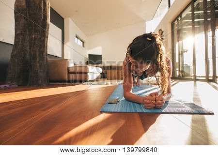 Woman Exercising And Looking At Her Mobile Phone