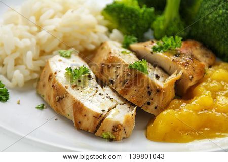 chicken breast fillet with fruity mango chuntey broccoli and rice on a white plate closeup with selected focus and narrow depth of field
