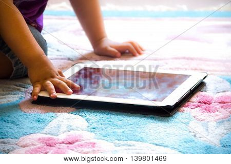 Baby boy sitting on floor playing with tablet pc. Close-up photo of the hands. Little touch pad early learning.