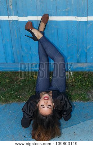 Young sexy suntanned woman in a short top shirt and leggins on high heels with beautiful modern make-up and hair posing against blue painted wooden wall
