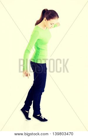 Attractive woman standing and looking down, touching copy space.