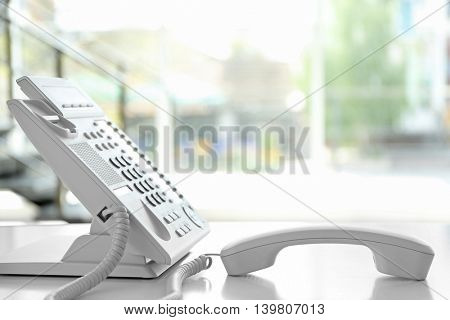 Modern office IP telephone set on light blurred background