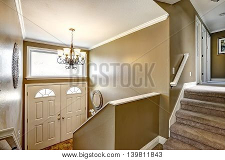 Entryway In American Home With Mocha Walls And Staircase