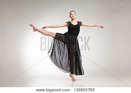 Young ballet dancer wearing black transparent dress dancing over white background