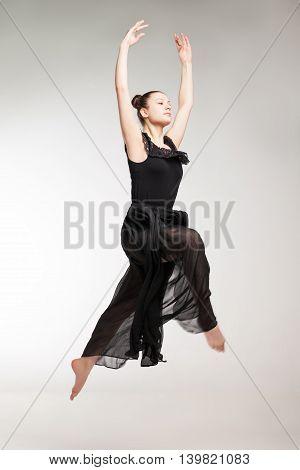 Young ballet dancer wearing black transparent dress jumping over white background