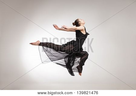 Young ballet dancer wearing black transparent dress jumping over white background