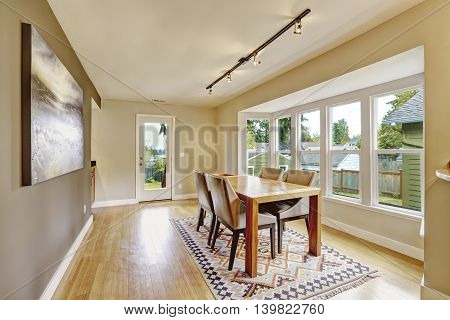 Cozy Creamy Tones Dining Room With Wooden Table Set.