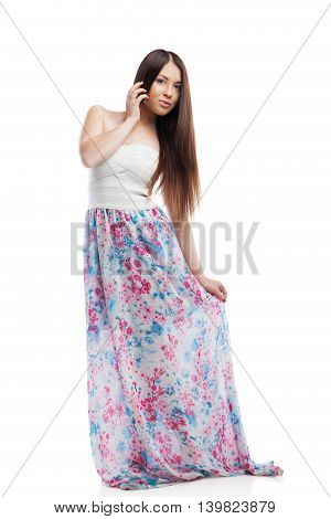 Young woman with beautiful long hair posing in long dress her hand touching the dress. Isolated, on white background