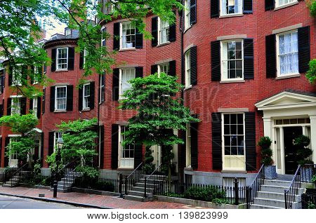 Boston Massachusetts - July 14 2013: 19th century brick homes with front curved bow bays line historic Louisburg Square on Beacon Hill
