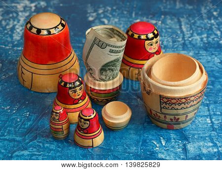 Group nesting dolls and ten dollars on a blue background